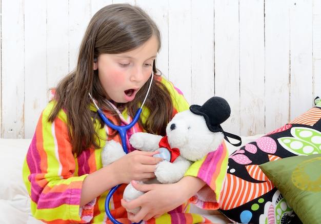 Больная маленькая девочка играет со своим мишкой
