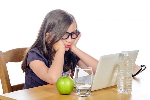 Усталая молодая девушка перед своим ноутбуком
