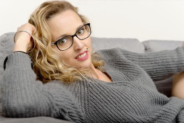 Привлекательная белокурая женщина расслабляющий на диване в своем доме