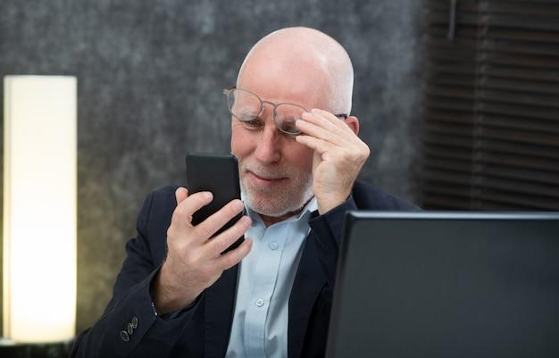 スマートフォンを使用して上級ビジネスマン、彼は困難と視覚の問題を抱えています。