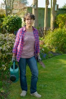 彼女の美しい庭でガーデニングの女性。