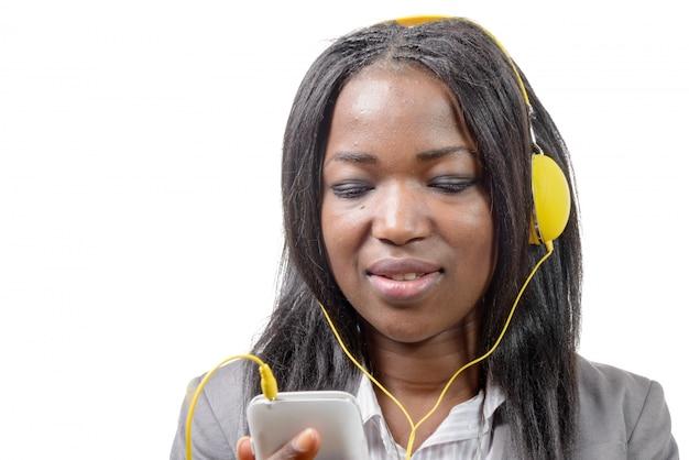 Африканская девушка держит мобильный телефон и слушать музыку