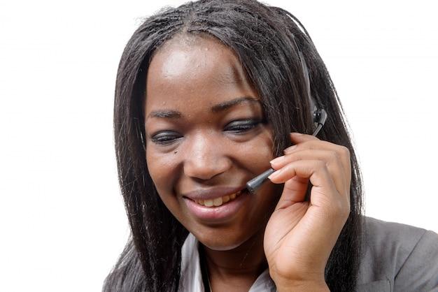 Портрет усмехаясь жизнерадостного африканского оператора телефона поддержки в шлемофоне.