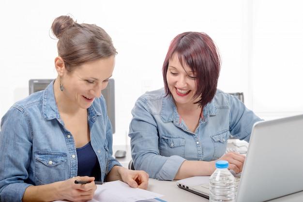 Колледж двух женщин работает на ноутбуке