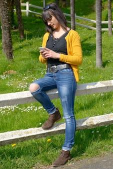 外の公園で携帯電話を持つ若いブルネットの少女