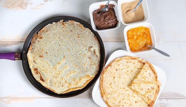 チョコレートシュガーと白い木製のテーブルの上のジャムのおいしいパンケーキ