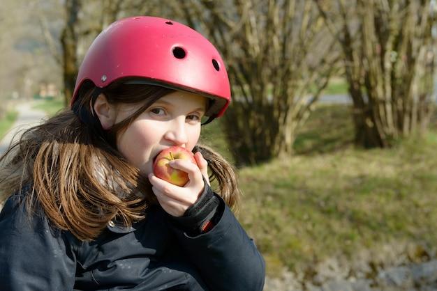 ローラースケートのプレティーン、リンゴを食べる