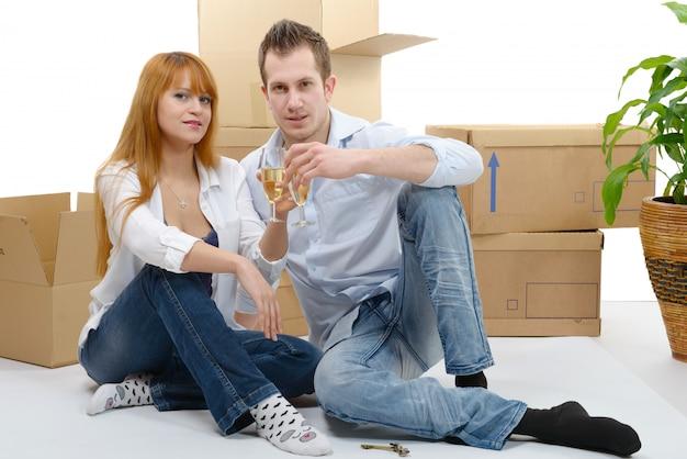 Пара празднует свой новый дом, ключи и шампанское в руке.