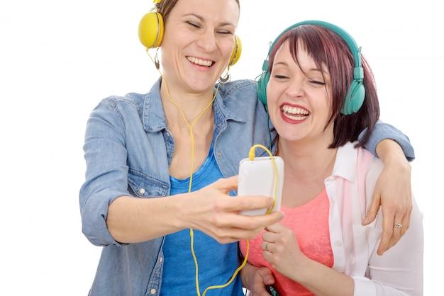 Молодые улыбающиеся женщины, принимающие селфи.