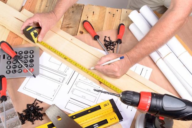 男は様々な大工道具で家具を作った