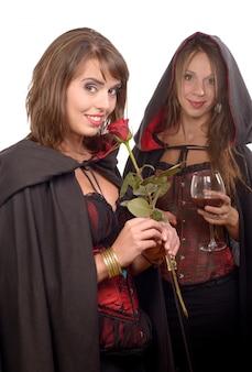 Замаскированные молодые женщины хэллоуин со стаканом крови и розой