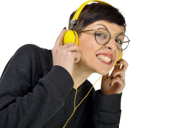 Наушники молодой женщины нося слушая к музыке