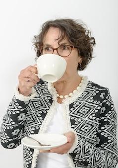 お茶を飲むエレガントな成熟した女性