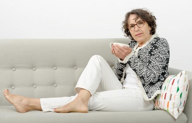 ソファでお茶を飲む熟女