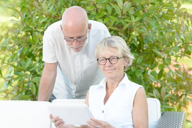 Пара пожилых людей смотрит на цифровой планшет