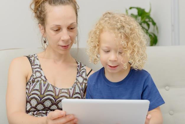 金髪の少年と彼の母親のデジタルタブレット