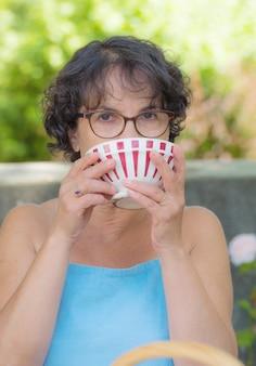 お茶を一杯飲むメガネの女性