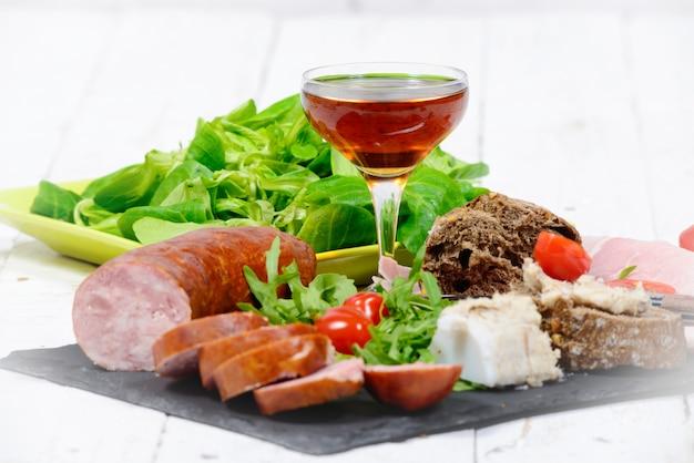 Колбасная тарелка с бокалом вина
