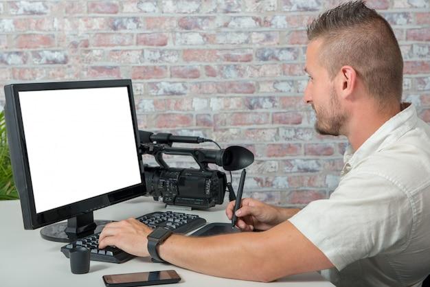 グラフィックタブレットとプロのビデオカメラを持つ男のビデオエディタ