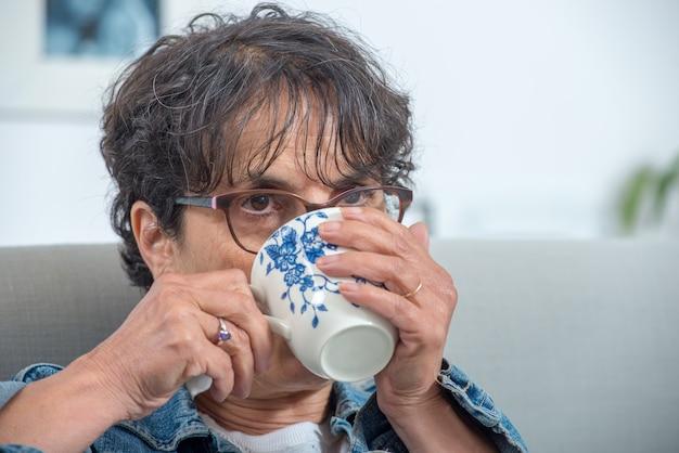 Чашка чая красивой зрелой женщины выпивая