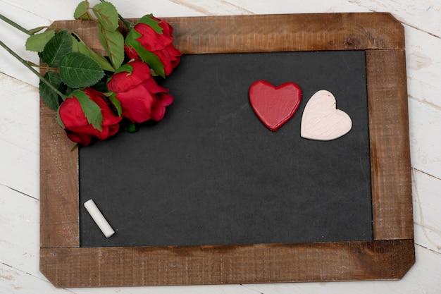 Концепция романтика, маленькая классная доска, розы и сердце