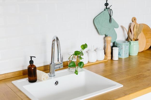 スカンジナビアスタイルの白いキッチン、キッチンの詳細、木製のテーブルの上の植物を見る