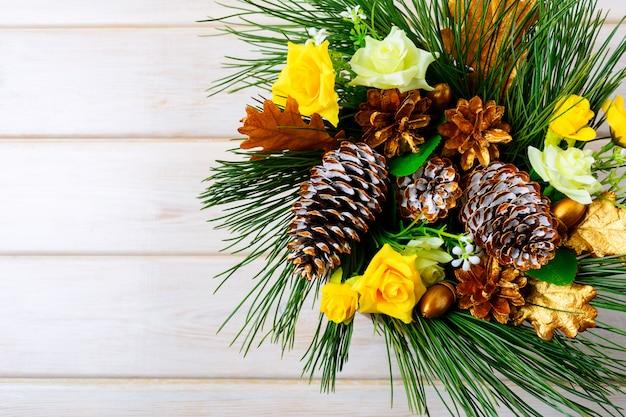 Новогоднее украшение с желтыми шелковыми розами и золотыми шишками
