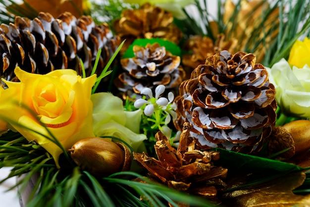 Новогоднее украшение с золотыми еловыми шишками и шелковыми розами