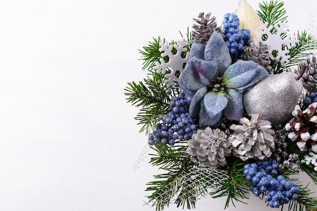 Новогодний фон с синими шелковыми пуансеттиями и серебряной грушей с блестками