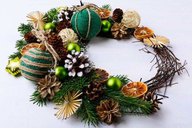 素朴なジュート麻ひもで飾られた装飾品と乾燥オレンジのクリスマスリース