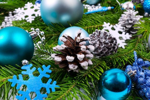 Рождественский фон с украшенными сосновыми шишками, бирюзовыми шарами и синей снежинкой