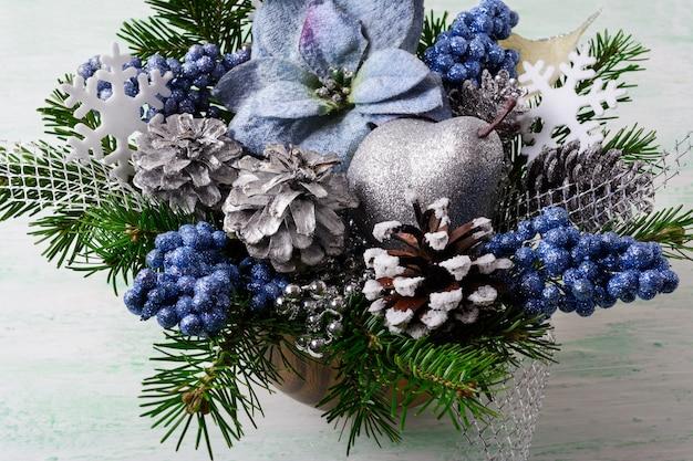Новогодний фон с голубыми шелковыми пуансеттиями и блестящими ягодами