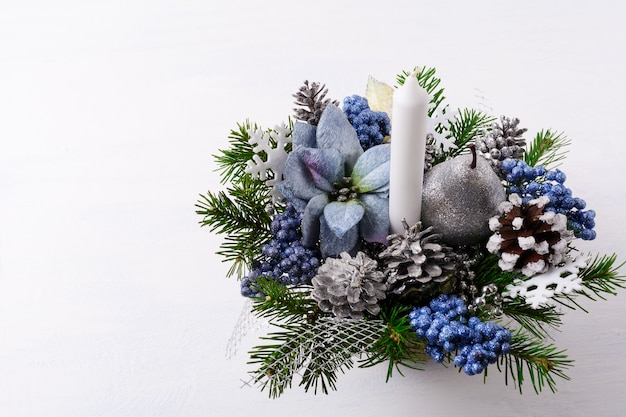 Рождественский фон со свечой и голубыми шелковыми пуансеттиями
