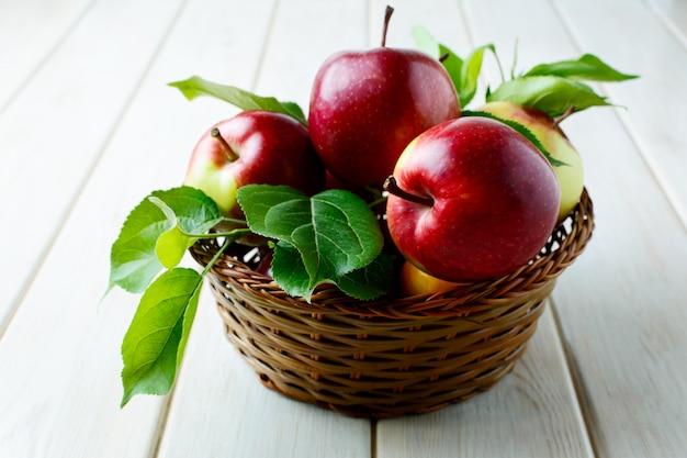 木製のテーブル上のバスケットの葉と熟したリンゴ