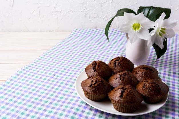 チョコレートカップケーキと白い花のプレート、コピースペース