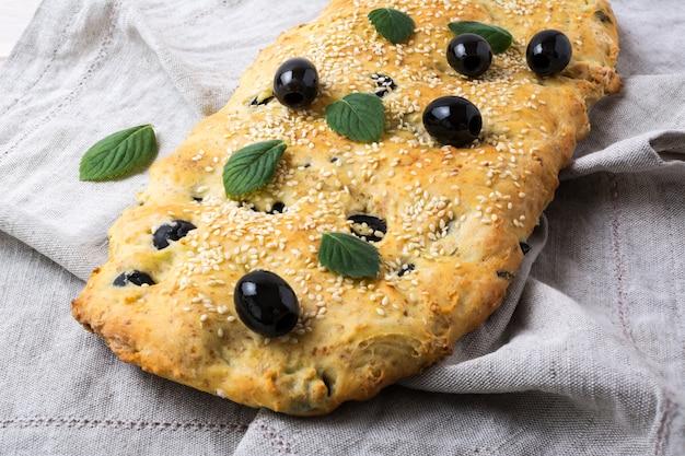 リネンのナプキンにオリーブ、ニンニク、ハーブ入りイタリアのパンのフォカッチャ