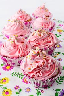 ホイップクリームとピンクのバースデーカップケーキ