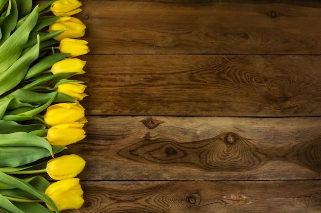木製の表面に黄色のチューリップの束