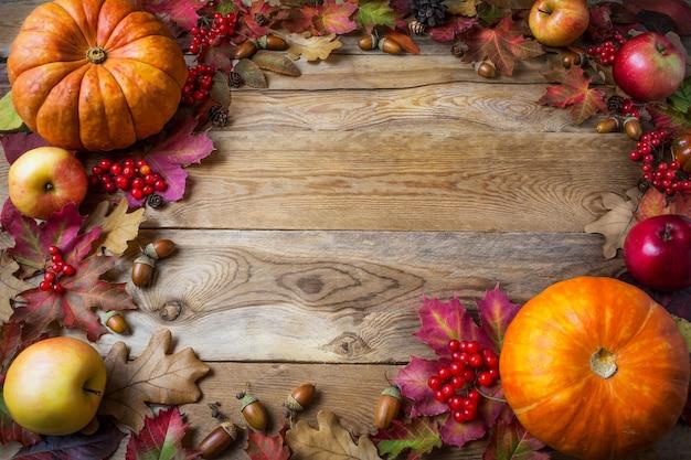 木製の背景にカボチャ、リンゴ、ドングリ、果実、紅葉のフレーム