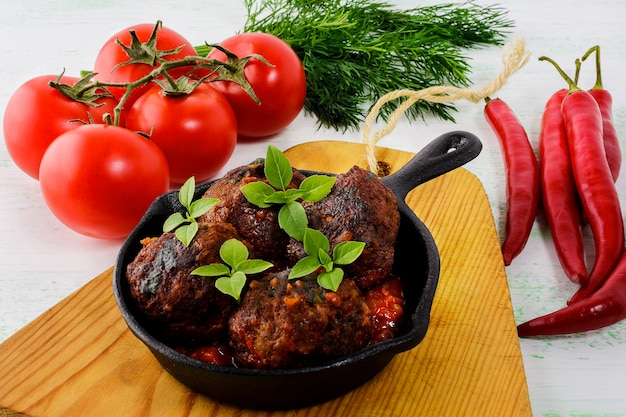 Фрикадельки с перцем чили и помидорами в чугунной сковороде