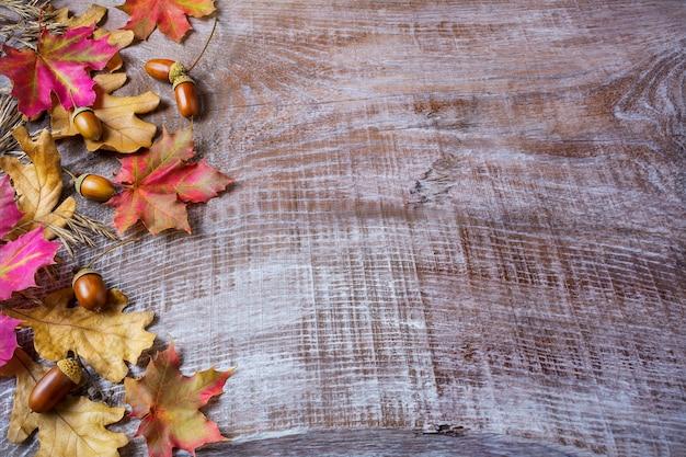 木製の背景にドングリと秋の葉の感謝祭のコンセプト