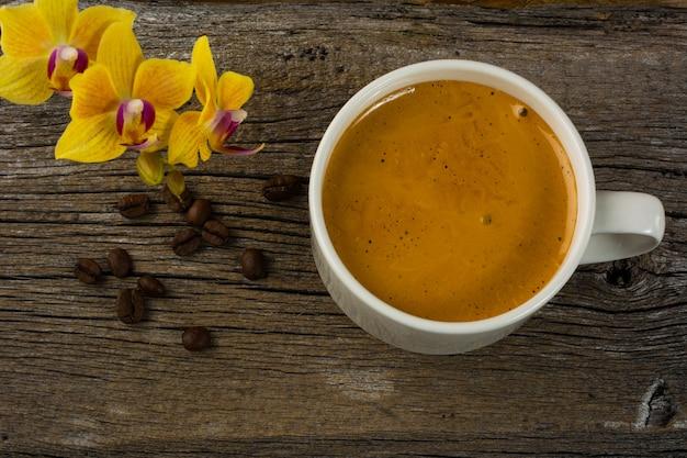 コーヒーマグと木製の背景に黄色の蘭