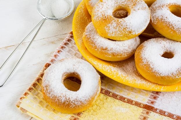 Домашние сладкие пончики с сахарной пудрой на клетчатой салфетке