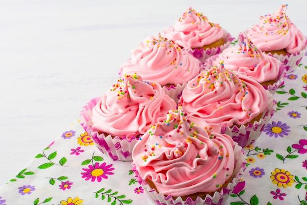 花のナプキンにピンクのカップケーキ