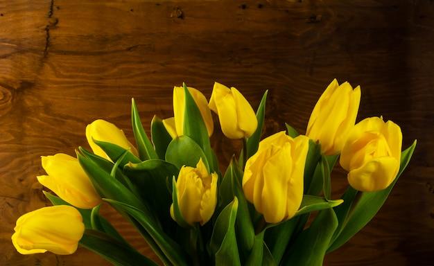 木製の背景に春の黄色の花束
