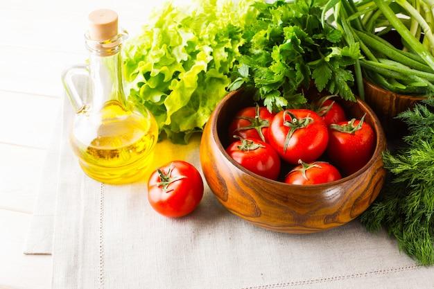 白い木製の背景に野菜とオリーブオイル