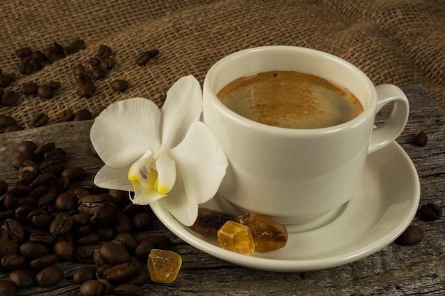 濃い朝のコーヒーとコーヒー豆の白いカップ