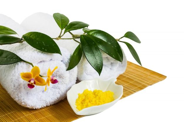 白で隔離される黄色の化粧用塩とスパのコンセプト
