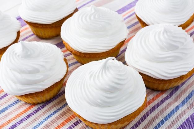 リネンナプキンの上面に白いカップケーキ
