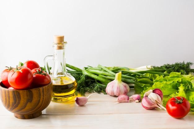 Оливковое масло, чеснок и помидор на белом фоне деревянные